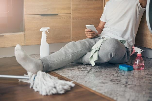 Skoncentrowane zdjęcie na mężczyźnie siedzącym na podłodze i rozmawiającym online podczas korzystania ze smartfona