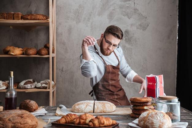Skoncentrowanego mężczyzna piekarniana pozycja przy piekarnią blisko chleba