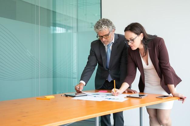 Skoncentrowani biznesmeni oglądający dokumenty statystyczne i robiąc notatki