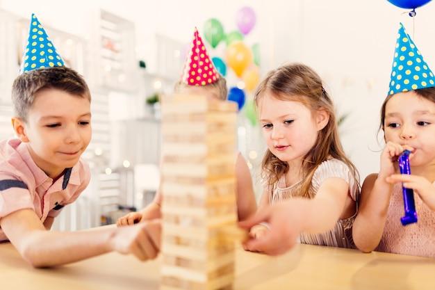 Skoncentrowani dzieci bawią się z grą