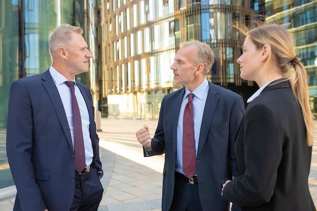 Skoncentrowani koledzy biznesowi stojąc i rozmawiając na zewnątrz, wspólnie omawiając projekt. koncepcja pracy zespołowej i komunikacji