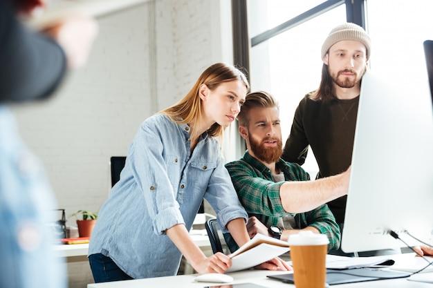 Skoncentrowani koledzy w biurze za pomocą komputera