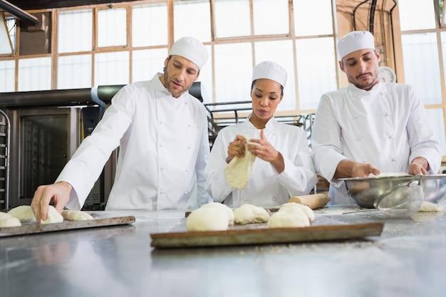Skoncentrowani koledzy wyrabiający niegotowane ciasto