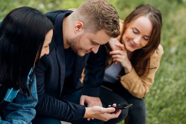 Skoncentrowani ludzie siedzą i korzystają z telefonu komórkowego