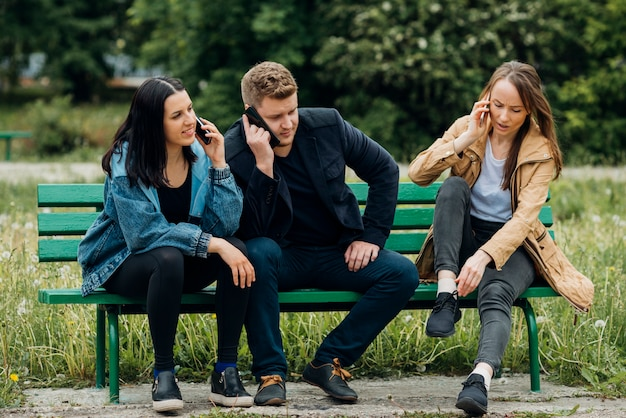 Skoncentrowani ludzie siedzą na ławce i rozmawiają przez telefon komórkowy
