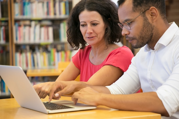Skoncentrowani ludzie studiujący z laptopem razem