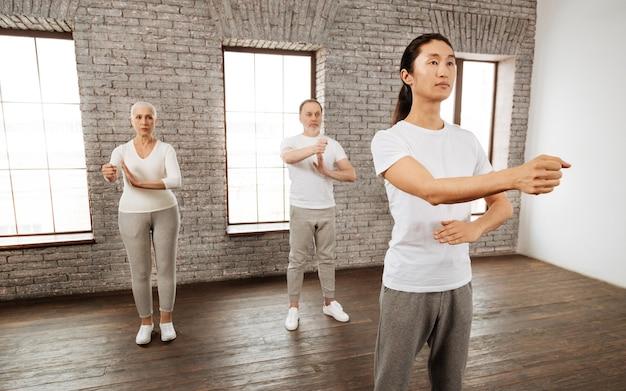 Skoncentrowani ludzie w białych koszulkach i szarych spodniach stoją na środku pokoju w pozycjach jogi, patrząc prosto