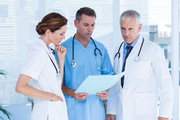 Skoncentrowani medyczni koledzy analizuje kartotekę wpólnie