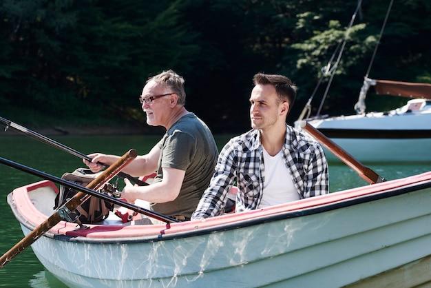 Skoncentrowani mężczyźni z wędką siedzący na łodzi