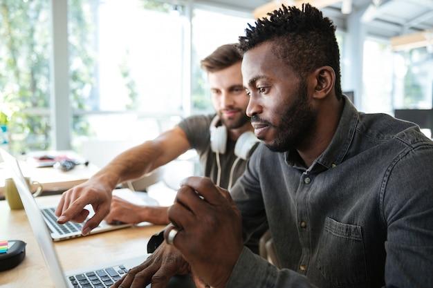 Skoncentrowani młodzi koledzy siedzi w biurowym coworking