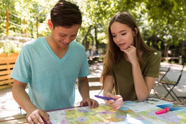 Skoncentrowani młodzi wieloetniczni przyjaciele uczniowie na zewnątrz