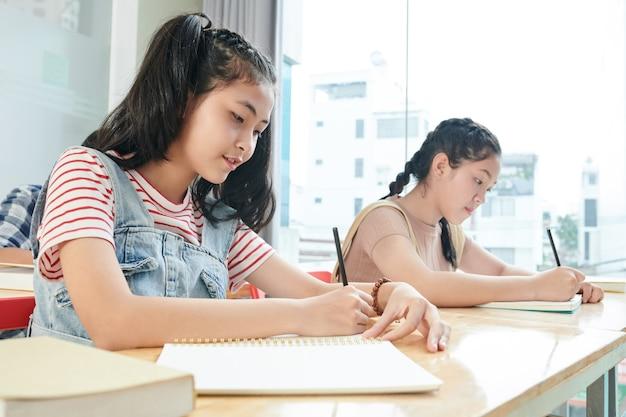 Skoncentrowani nastoletni uczniowie piszący w zeszytach podczas zajęć w szkole