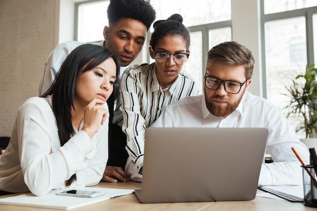 Skoncentrowani poważni młodzi biznesowi koledzy używa laptop.