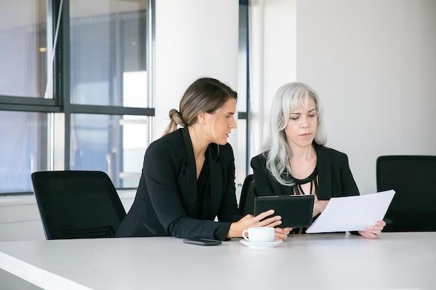 Skoncentrowani profesjonaliści wspólnie analizujący raporty. dwie kobiety biznesu siedzą razem, czytają dokumenty, używają tabletu i rozmawiają. koncepcja pracy zespołowej