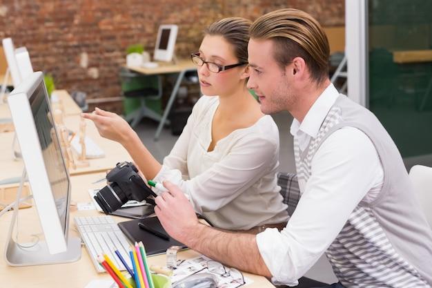 Skoncentrowani przypadkowi fotografia redaktorzy używa komputer w biurze