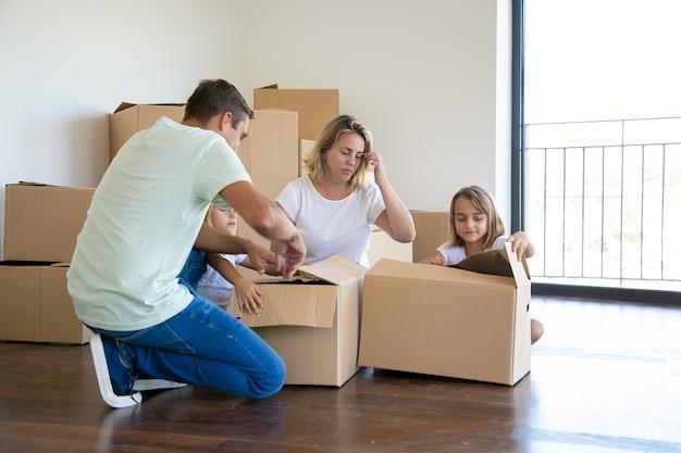 Skoncentrowani rodzice i dzieci rozpakowują rzeczy w nowym mieszkaniu, siadają na podłodze i otwierają pudełka