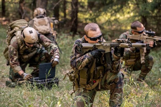 Skoncentrowani snajperzy siedzą na ziemi i patrzą przez lunety, chroniąc jednocześnie hakera przed wrogiem w lesie