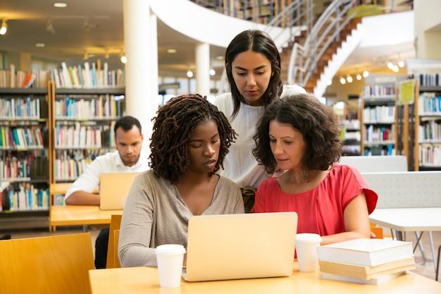 Skoncentrowani studenci pracujący nad nowym projektem w bibliotece