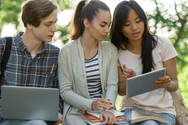 Skoncentrowani uczniowie siedzący i studiujący na zewnątrz