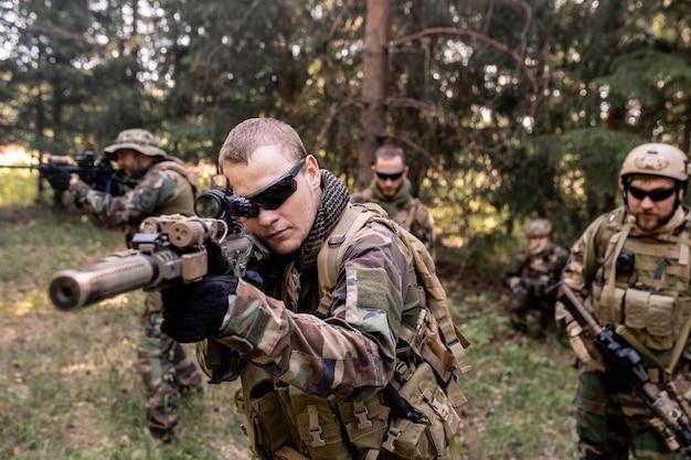 Skoncentrowani uzbrojeni żołnierze w mundurach noszący karabiny i badający teren leśny