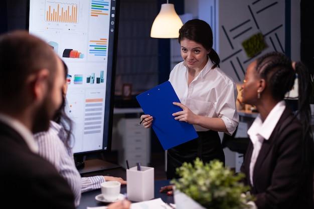 Skoncentrowani, wieloetniczni biznesmeni pracujący w biurze spotkań firmowych, zarządzanie burzą mózgów ...