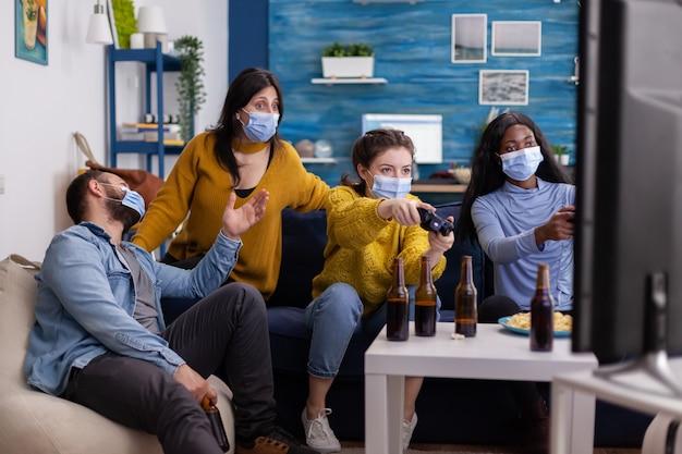 Skoncentrowani wielorasowi przyjaciele grający w gry wideo za pomocą joysticka w salonie, noszący maskę na twarz, aby zapobiec rozprzestrzenianiu się koronawirusa. różnorodni ludzie bawią się, śmieją na nowej normalnej imprezie