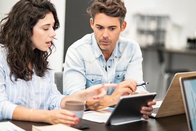 Skoncentrowani współpracownicy coworkingowi rozmawiający o kwestiach finansowych