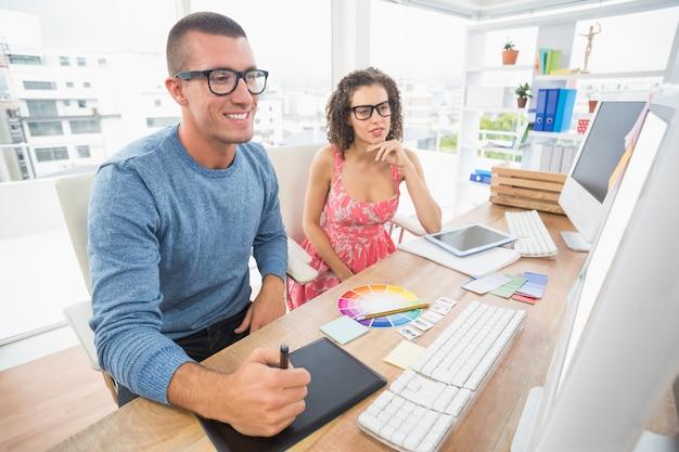 Skoncentrowani współpracownicy za pomocą laptopa i digitizera