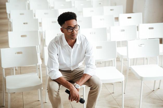 Skoncentrowany afrykański mężczyzna siedzi w biurze indoors