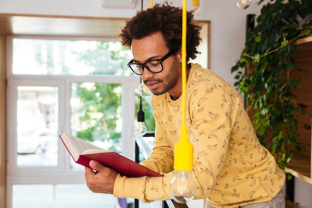Skoncentrowany afrykański młody mężczyzna w okularach stojący i czytający książkę w domu
