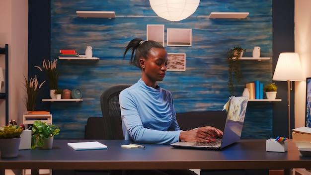 Skoncentrowany afrykański niezależny piszący na komputerze i używający karteczek samoprzylepnych do listy zadań, umieszczając go na laptopie siedzącym na biurku w salonie pracy późno w nocy. czarna kobieta pracuje w nadgodzinach w domu