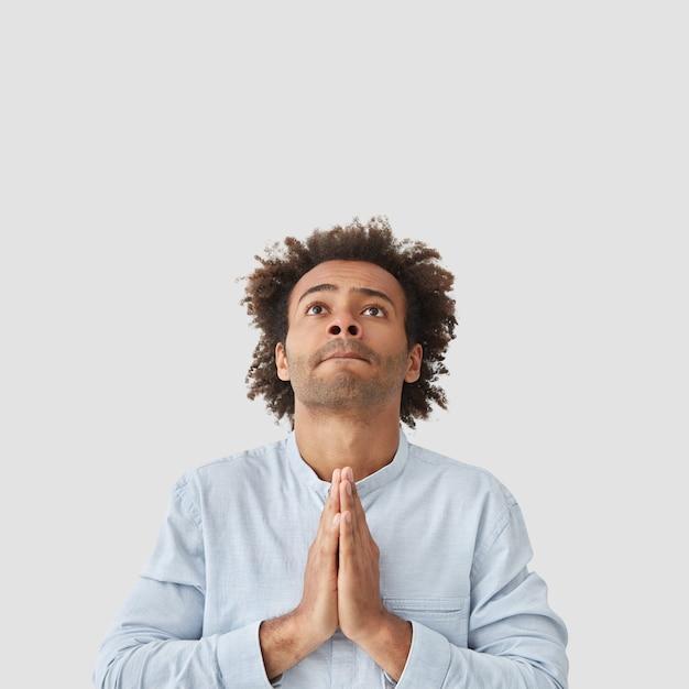 Skoncentrowany atrakcyjny mężczyzna student wykonuje gest modlitwy, patrzy z nadzieją w górę