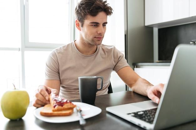 Skoncentrowany atrakcyjny mężczyzna używa laptop podczas gdy jedzący śniadanie