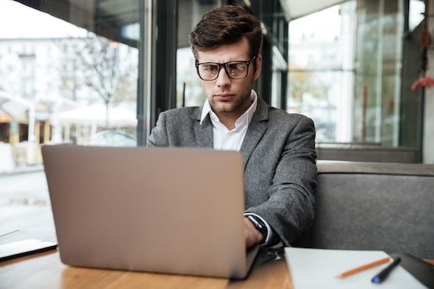 Skoncentrowany biznesmen siedzi stołem w kawiarni i używa laptop w okularach
