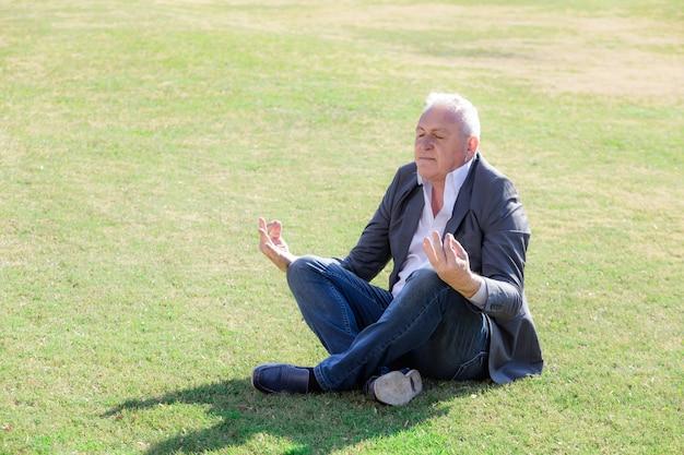Skoncentrowany biznesmen siedzi w pozycji jogi