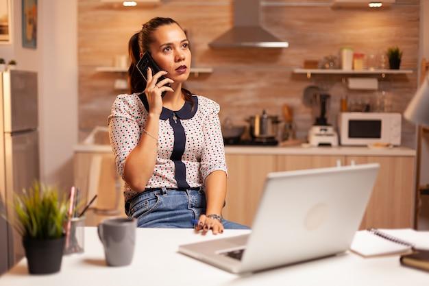 Skoncentrowany bizneswoman podczas rozmowy telefonicznej późno w nocy z domowego biura. pracownik korzystający z nowoczesnych technologii o północy wykonujący nadgodziny w pracy, firmie, zajęty, karierze, sieci, stylu życia, bezprzewodowo.
