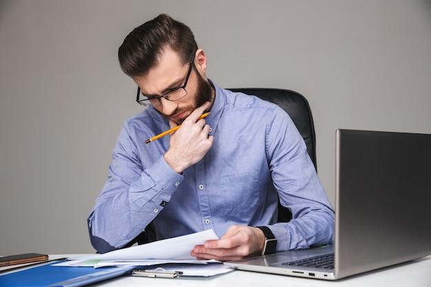 Skoncentrowany brodaty elegancki mężczyzna w okularach czytający coś siedząc przy stole w biurze