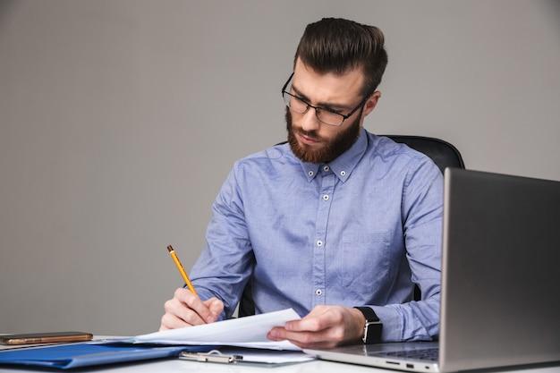 Skoncentrowany brodaty elegancki mężczyzna w okularach pisze coś siedząc przy stole w biurze