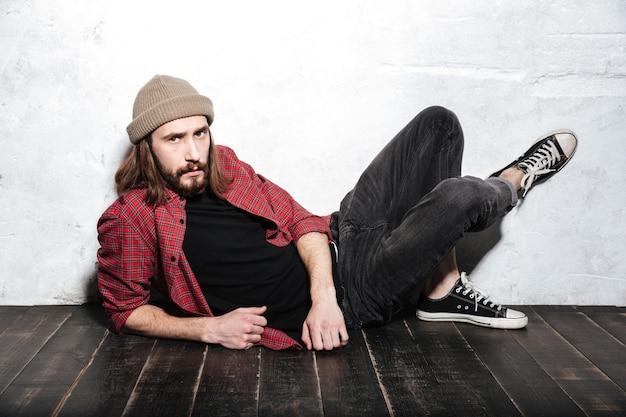 Skoncentrowany brodaty hipster w kapeluszu ubrany w koszulę w klatce leży na podłodze, pozując nad ścianą