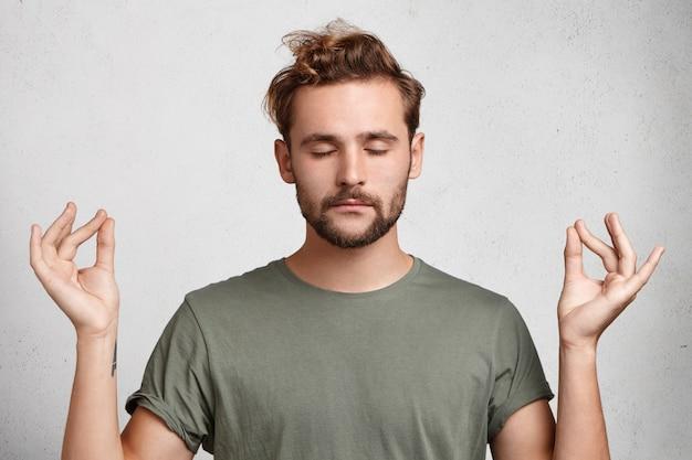 Skoncentrowany, brodaty mężczyzna o atrakcyjnym wyglądzie medytuje