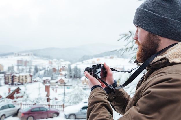 Skoncentrowany brodaty młody mężczyzna robi zdjęcia widoków na zewnątrz w zimie