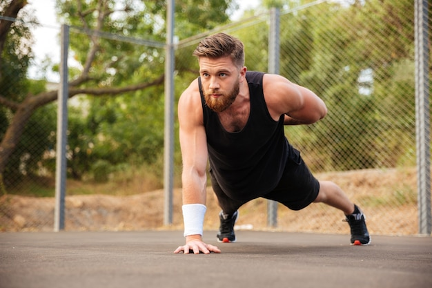 Skoncentrowany brodaty młody sportowiec robi pompki jedną ręką na świeżym powietrzu