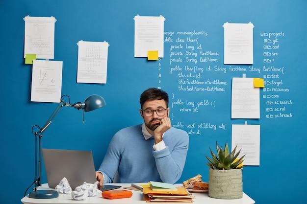 Skoncentrowany, brodaty web developer ulepsza nową wersję strony, siedzi przy białym stole, załadowany notatnikami, przekąską, filiżanką herbaty i doniczkową rośliną, ze smutkiem patrzy na problem z projektem, pochyla się do ręki