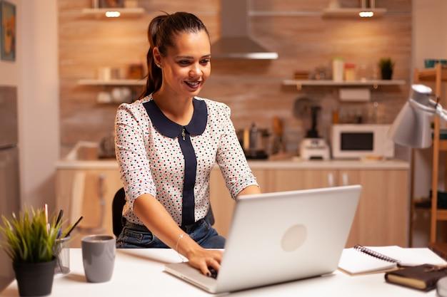 Skoncentrowany businesswoman uśmiechnięty pracy późno w nocy przy użyciu laptopa w kuchni. pracownik korzystający z nowoczesnych technologii o północy wykonujący nadgodziny dla pracy, biznesu, zajęty, kariery, sieci, stylu życia.