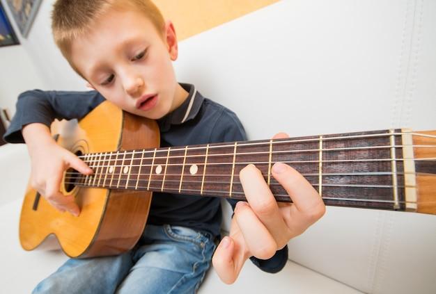 Skoncentrowany chłopiec ćwiczy z gitarą akustyczną siedzącą na kanapie w domu
