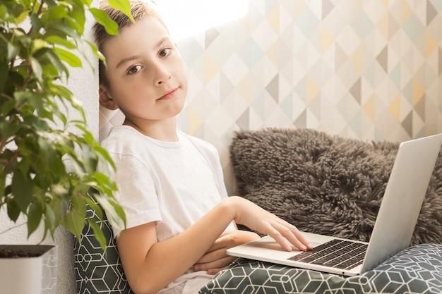Skoncentrowany chłopiec siedzi przy biurku z laptopem i odrabia lekcje