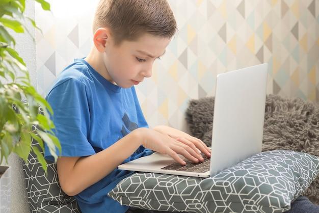 Skoncentrowany chłopiec siedzi przy biurku z laptopem i odrabia lekcje.