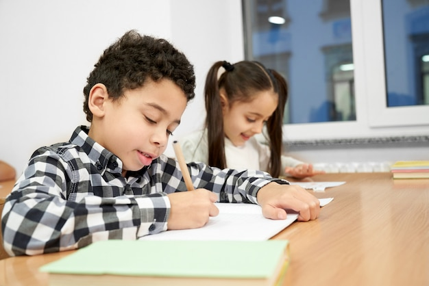 Skoncentrowany chłopiec siedzi przy stole i pisze w zeszyt