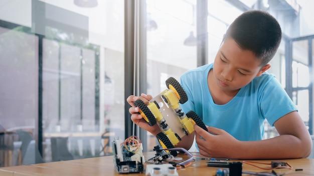 Skoncentrowany chłopiec tworzy robota w laboratorium.