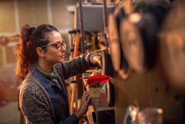 Skoncentrowany cieśla kobieta w średnim wieku, patrząc na niektóre rzeczy w pudełku z materiałem.